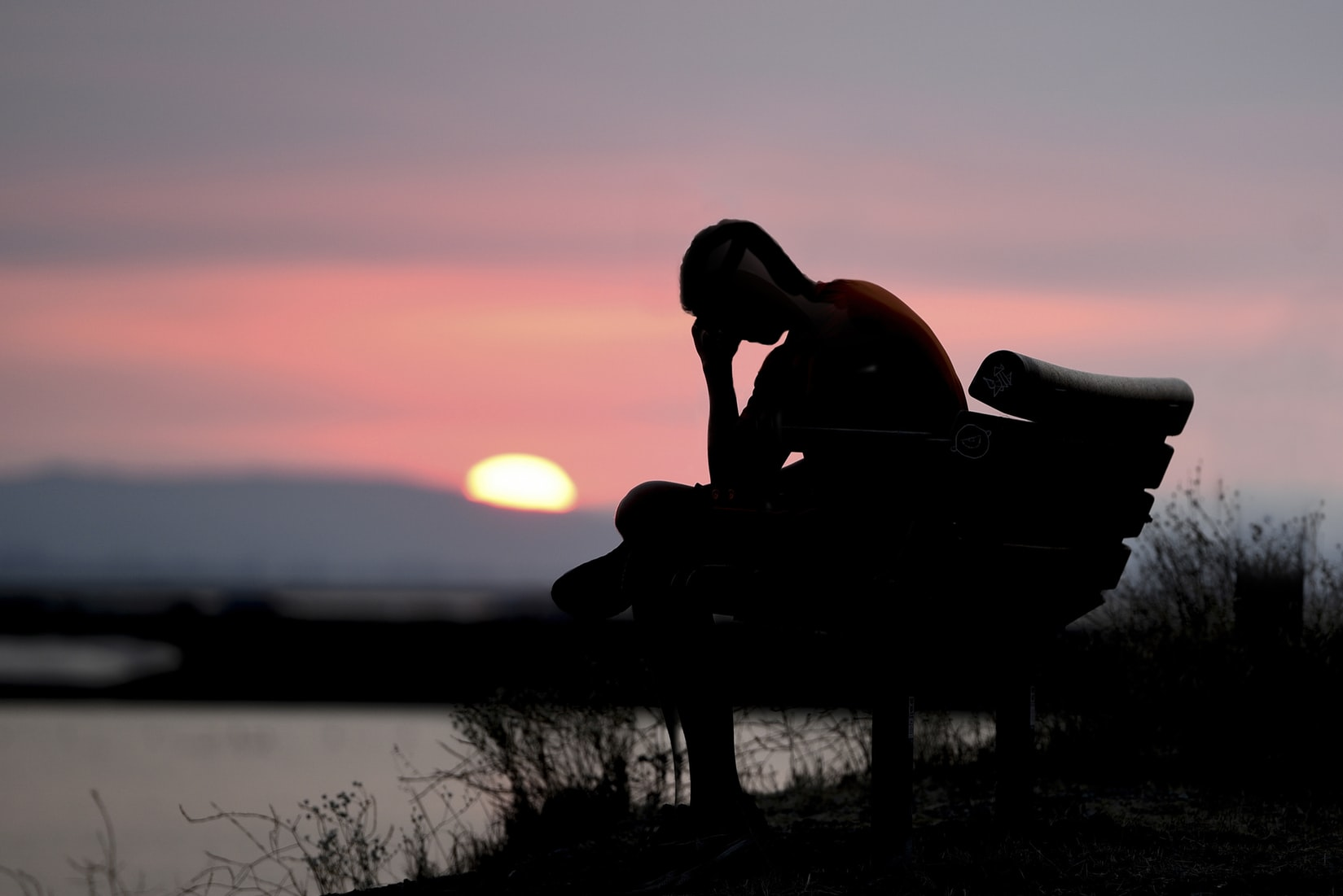 Silhouette of contemplative man on a bench at sunset.